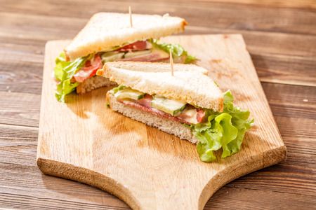 Fresh sandwiches on wooden board