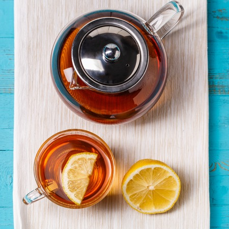 chillout: Glass cup of tea with lemon and glass teapot. Stock Photo