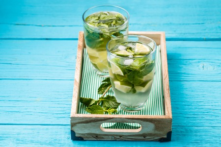 Two glasses of mojito in wooden box with mint
