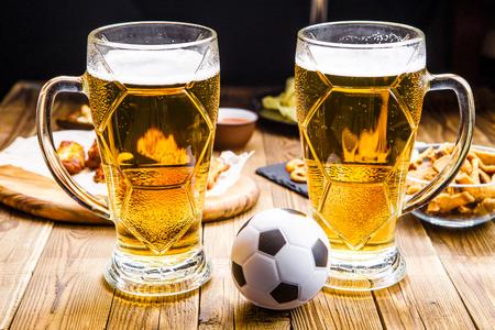Appetizers en bier op de tafel voor de voetbalwedstrijd kijken.