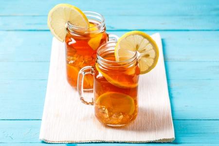 Iced tea in a glass jar with lemon.