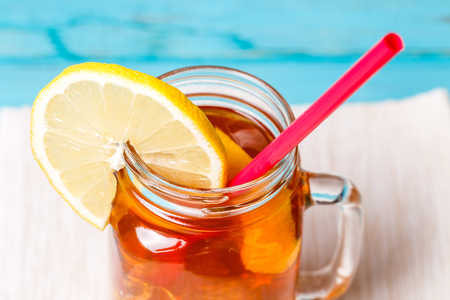 Iced tea in a glass jar with lemon.