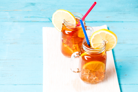 water cooler: Iced tea in a glass jar with lemon.