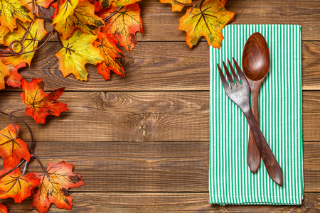 Wooden table with fork , spoon on napkin, with maple leaves