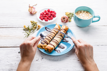 Twisted pancakes watered with chocolate Stock Photo