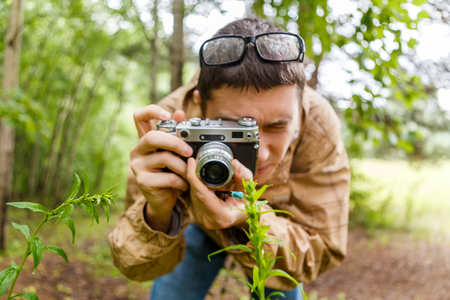 Photo of man with camera in woods