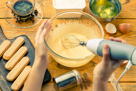 Photo of man with whisk preparing dessert of cookies