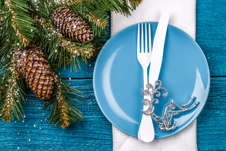 grunge cutlery: Christmas table place setting - blue table with white napkin, blue plate, white fork and knife, decorated christmas tree toy - silver deer and christmas pine branches. Stock Photo