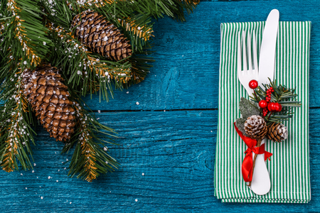 grunge cutlery: Christmas table place setting - blue table with green napkin, white fork and knife, decorated sprig of mistletoe and christmas pine branches. Stock Photo