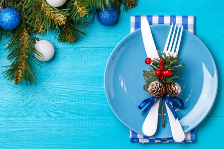 Christmas table place setting with napkin, blue plate, white fork and knife, decorated sprig of mistletoe and christmas pine branches.