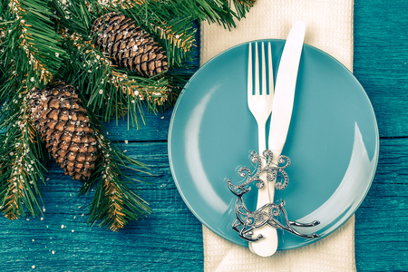 grunge cutlery: Christmas table place setting - blue table with white napkin, blue plate, white fork and knife, decorated christmas tree toy - silver deer and christmas pine branches. Toned photo