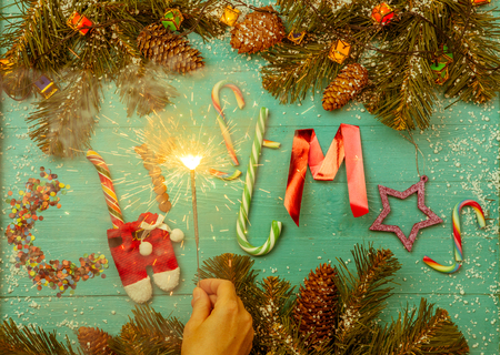 Photo of burning garland, fir branches, words christmas
