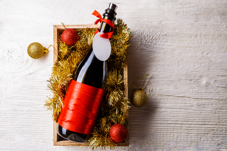 Image of bottle of wine in box with tinsel, Christmas balls Foto de archivo