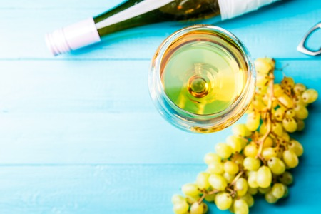 Photo on top of glass with juice, grape, bottle on blue wooden table