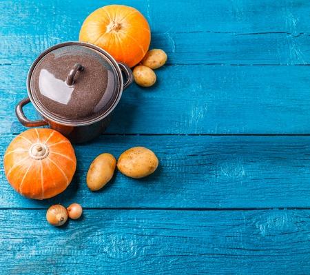 Photo of pot with lid, potatoes, pumpkins, onions Stock Photo