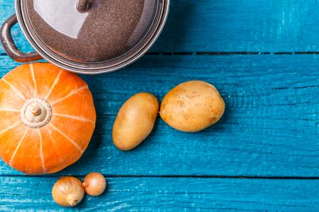 Image of pot with lid, potatoes, pumpkin, onions