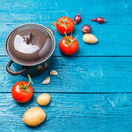 Picture of iron pot, tomato, potatoes, onions on blue wooden background.