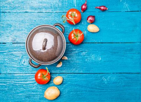 Foto oben auf Eisentopf, Tomate, Kartoffel, Zwiebel auf blauem hölzernem Hintergrund. Standard-Bild - 89883229