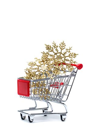 Shopping cart with golden snowflakes on the empty white