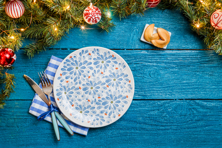 Photo of New Year branches of fir, cookies with prediction, plates, forks, knife, napkin