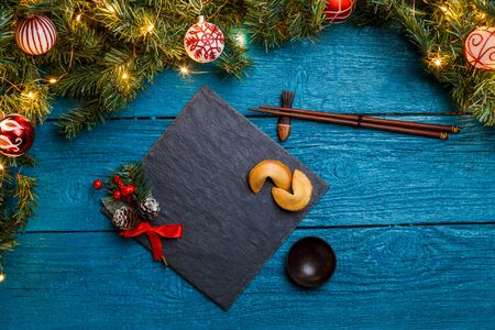 Photo of New Year branches of fir, black board, sticks for sushi, cookies with prediction