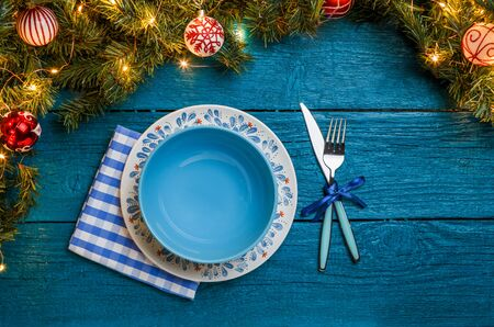 Photo of New Year branches of fir, plates, forks, knife, napkin