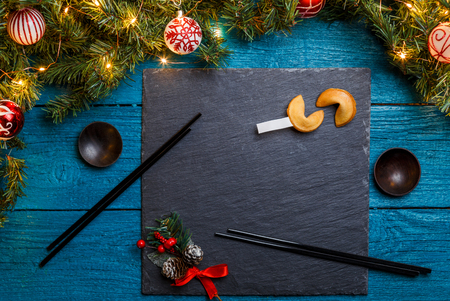 Image of New Year branches of fir, black board, sticks for sushi, cookies with prediction 스톡 콘텐츠