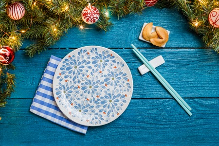Image of New Year branches of fir, cookies with prediction, plates, sticks for sushi Stock Photo
