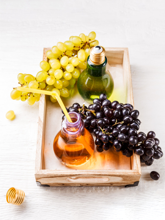 Picture from above of wooden tray with green and black grapes, two bottles of juice Stock Photo