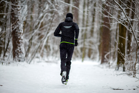 Photo from back of running athlete among trees in winter forest Stock Photo
