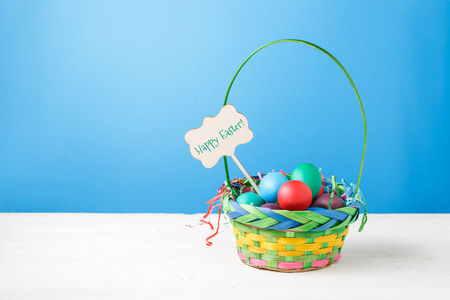 Picture of basket with colorful eggs with wish for happy Easter