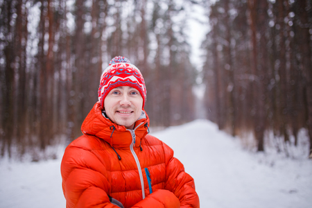 Photo of smiling man in winter forest in afternoon