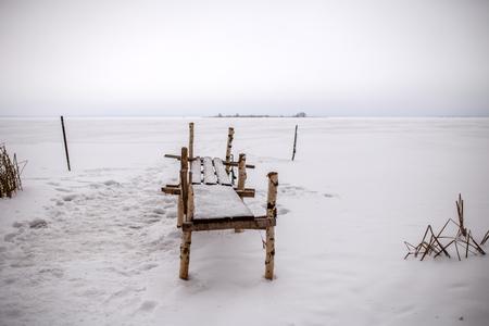 Photo of bench made of birch logs, snowy field