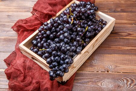 Image of black grapes in wooden box with claret cloth Stock Photo