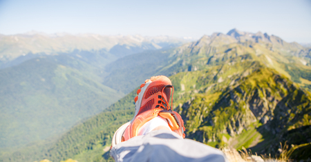 Picture of man in red sneakers and picturesque mountainous landscape Standard-Bild