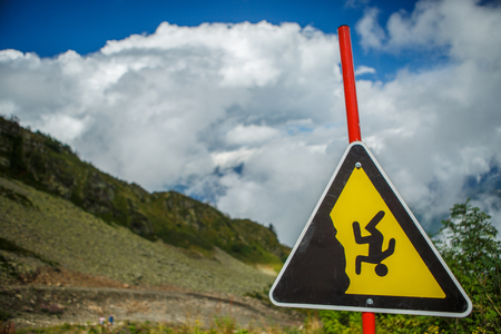 Image of mountain slope, cloudy sky and warning sign Stock fotó