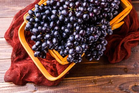 Image from above of black grapes in wooden basket with claret cloth Stock Photo