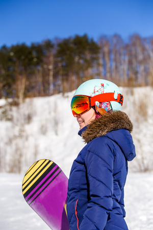 Side view of sporty woman wearing helmet with snowboard looking at camera