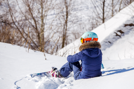 Photo from back of athlete in helmet sitting on snowy slope Stock Photo