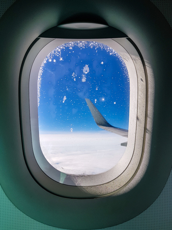 Photo of porthole with view to wing of airplane