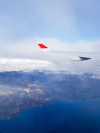 Image of wing of airplane, clouds, blue sky from window