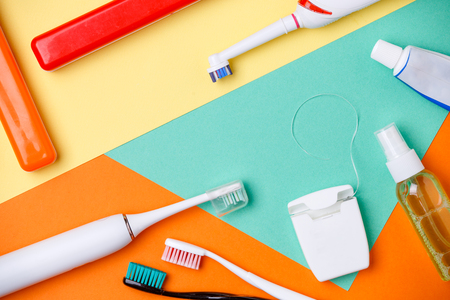 Picture of toothbrushes, tubes of pastes, floss on orange, green and yellow background
