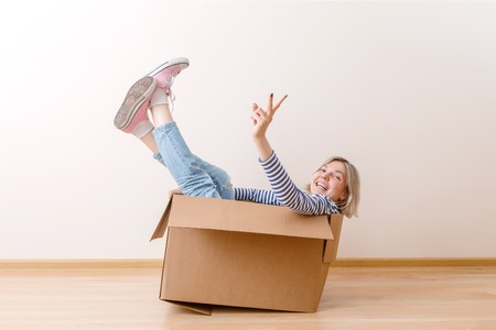 Photo of young woman sitting in cardboard box