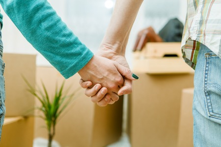 Photo of people holding hands in new apartment Stock Photo
