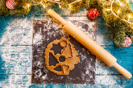 Photo of pine branches, dough, biscuit molds, rolling pin