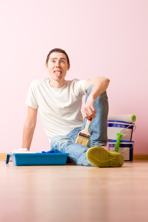Photo of man with brush sitting on floor