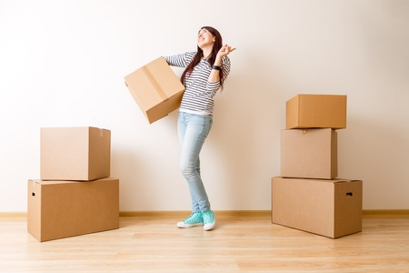 Image of young woman among cardboard boxes Foto de archivo