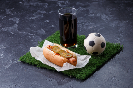 Photo of glass of beer, green grass with soccer ball, hotdog Фото со стока