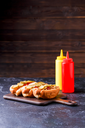 Image of hotdogs on cutting board at table