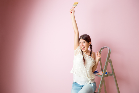 Image of cheerful woman with brush next to stepladder and roller against blank pink wall Stockfoto